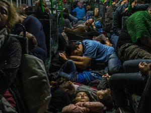 Grupo de refugiados dorme no chão de um ônibus após deixar Budapeste em direção à Viena, na Áustria (Foto Mauricio Lima - The New York Times - The Pulitzer Prize)